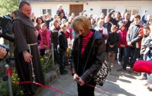 Palkó Cecília, a dévai gyermekotthon igazgatója vágja el a Szent Ferenc Alapítvány 20 évéről szóló kiállítás szalagját